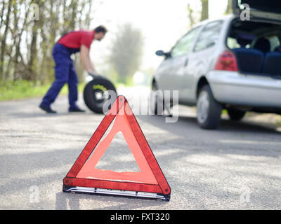 man repairing his car and a flat tire - Stock Photo