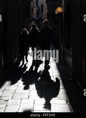 Pedestrians and their shadows in an alley, back lit, Venice, Veneto, Italy - Stock Photo