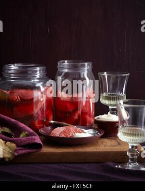 Dish and jars of homemade poached quince on cutting board - Stock Photo