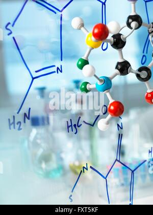 Ball and stick molecular model with formula of new drug written on glass - Stock Photo