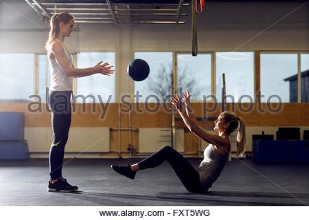 Two women throwing medicine ball in gym - Stock Photo
