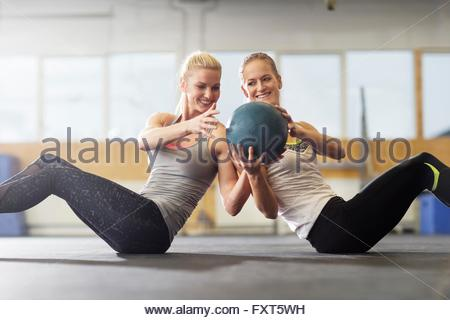 Two women passing medicine ball on gym floor - Stock Photo