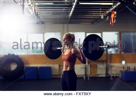 Woman lifting barbell on shoulders in gym - Stock Photo