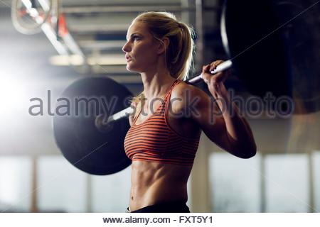 Mid adult woman lifting barbell on shoulders in gym - Stock Photo