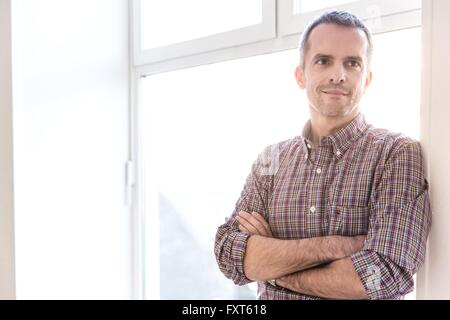 Mature man wearing check shirt leaning against window arms crossed looking away smiling - Stock Photo