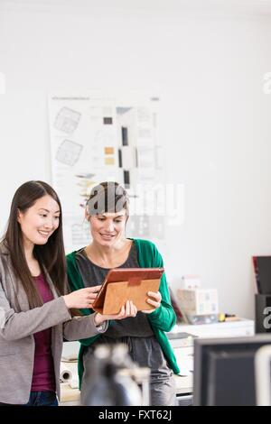 Colleagues in office using digital tablet smiling - Stock Photo