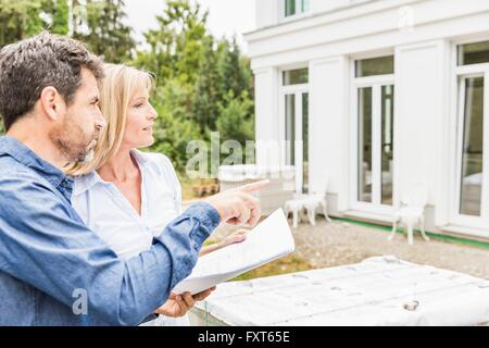 Architect showing homeowner plans for house exterior, looking away pointing - Stock Photo