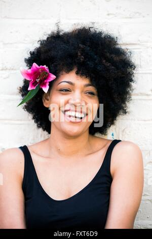 Portrait of woman with flower in hair - Stock Photo