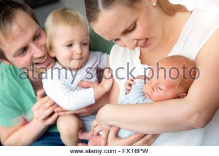 Mother, father and son cradling baby boy smiling - Stock Photo