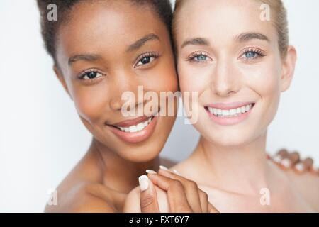Woman with hands on friends bare shoulders looking at camera smiling - Stock Photo