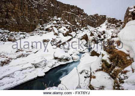 River flowing through rugged snow covered mountains, Thingvellir, Iceland - Stock Photo