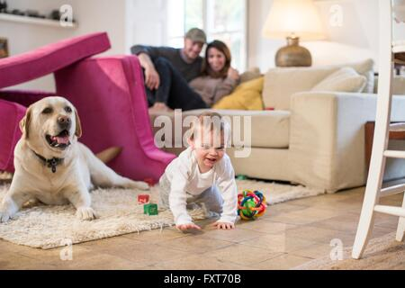 Baby boy and pet dog playing in fort made from sofa cushions - Stock Photo