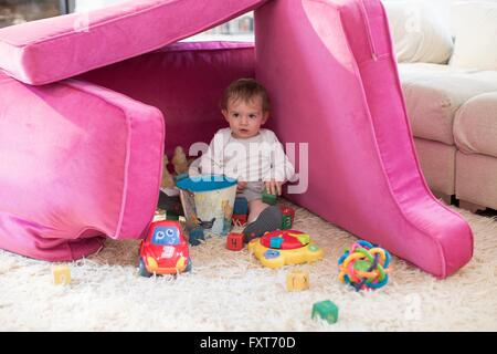 Baby boy playing in fort made from sofa cushions - Stock Photo