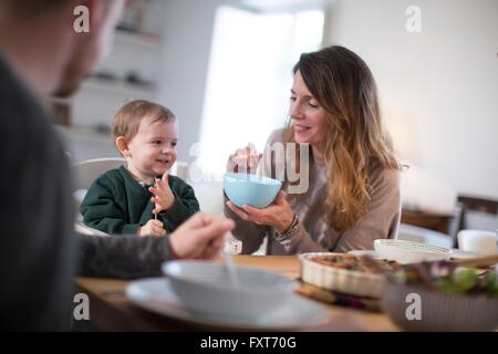 Parents at dining table feeding smiling baby boy - Stock Photo