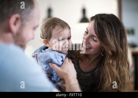 Mother holding smiling baby boy - Stock Photo