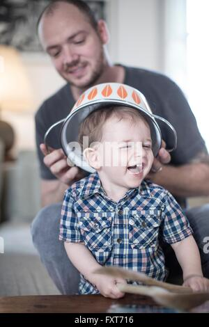 Father placing colander on smiling baby boys head - Stock Photo