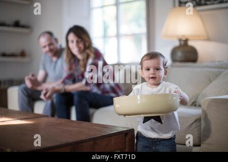 Baby boy in living room holding large bowl looking at camera smiling - Stock Photo