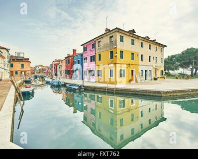 Traditional multi colored houses on canal waterfront, Burano, Venice, Italy - Stock Photo