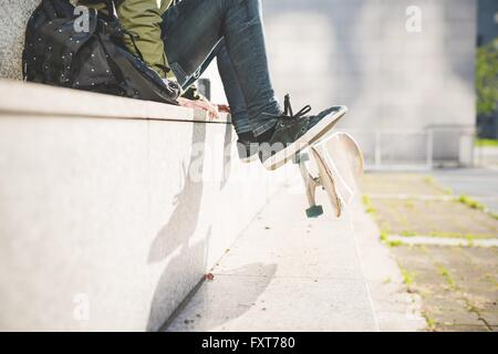 Waist down view of young male urban skate boarder sitting on wall flipping skateboard with feet - Stock Photo