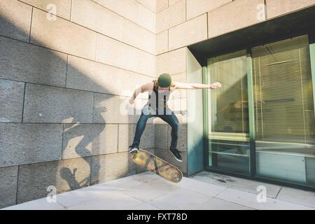 Young male urban skateboarder doing skateboarding jump trick in corner - Stock Photo