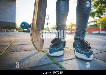 Legs and feet of young male urban skateboarder standing on sidewalk - Stock Photo