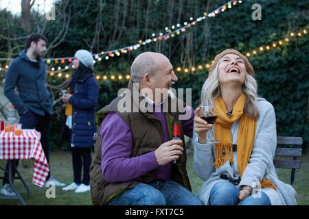 Mature couple at garden party throwing head back laughing - Stock Photo
