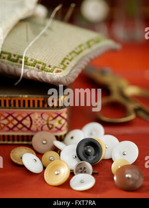 Vintage buttons and pin cushion on red table - Stock Photo