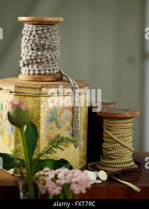 Vintage tin and traditional bobbins on table - Stock Photo