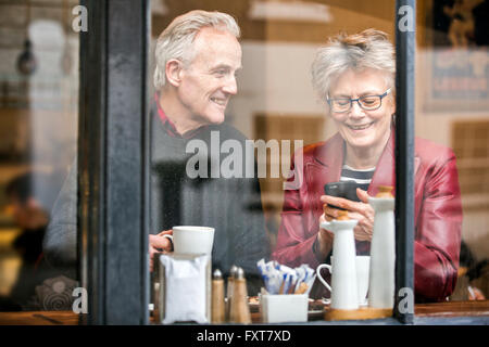 Senior couple in cafe window seat drinking coffee and texting on smartphone - Stock Photo