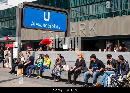 People sitting beside entrance to Alexanderplatz U Bahn station in Berlin Germany - Stock Photo