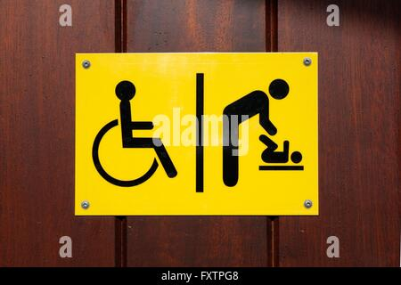 Yellow and black disabled and baby changing sign - Stock Photo