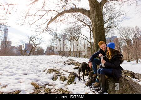 Young couple sitting with dog and drink flask in snowy Central Park, New York, USA - Stock Photo