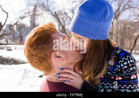 Romantic young couple kissing in snowy Central Park, New York, USA - Stock Photo