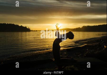 Woman practising yoga by lake at sunset - Stock Photo