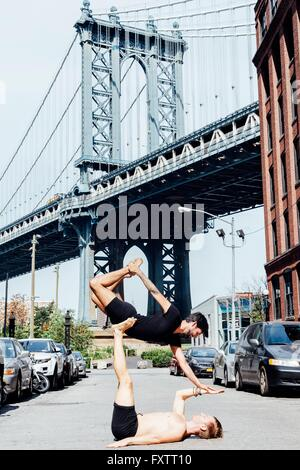Man balancing on top of another in yoga position by Manhattan Bridge, New York, USA - Stock Photo