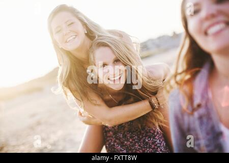 Woman on beach giving friend piggyback looking at camera smiling - Stock Photo