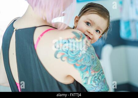 Portrait of baby boy peeking over his mothers tattoed shoulder - Stock Photo