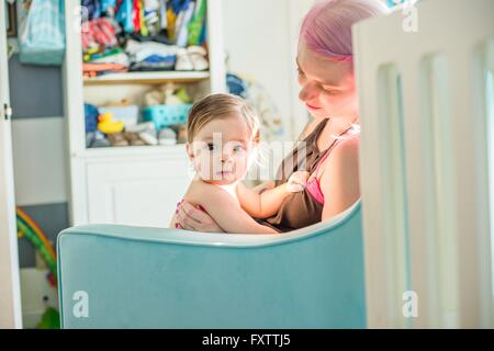 Mother sitting with baby son on nursery sofa - Stock Photo