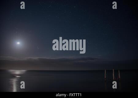 Starry sky and full moon illuminate iconic hammocks over waters, Isla Holbox, Mexico - Stock Photo