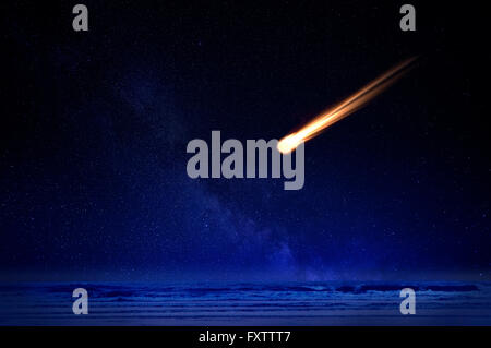 Meteor in night sky falling over ocean - Stock Photo
