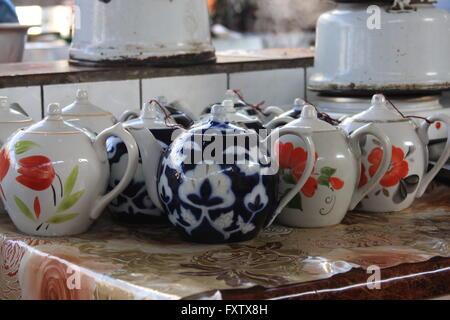 Teapots lined up, waiting to be served at a busy choyxana (teahouse) in Chorsu Bazaar.  Tashkent, Uzbekistan. - Stock Photo