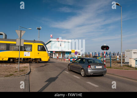 Car and train crossing level with closed boom barrier, railway and vehicle waiting in front of Szkuner building - Stock Photo
