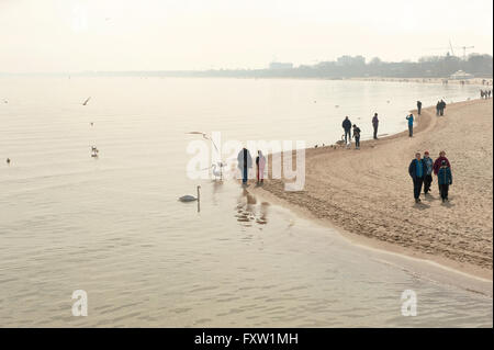 Hazy Sopot Beach view from pier, famous wooden walking jetty in Poland, Europe, early spring season, cold April - Stock Photo