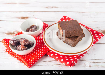 Healthy gluten free Paleo style brownies made with sweet potato, dates and almond flour on a white plate - Stock Photo