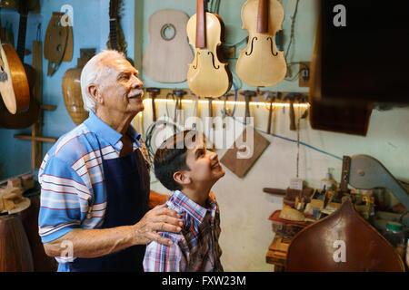 Small family business and traditions: old grandpa with grandson in lute maker shop. The senior artisan hugs the - Stock Photo