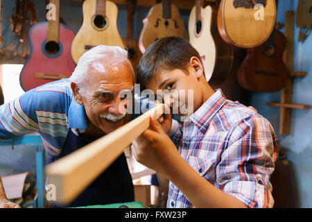 Small family business and traditions: old grandpa with grandson in lute maker shop. The senior artisan teaches to - Stock Photo