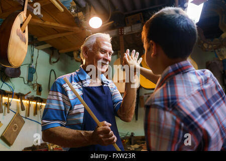 Small family business and traditions: old grandpa with grandson in lute maker shop. The senior artisan gives five - Stock Photo