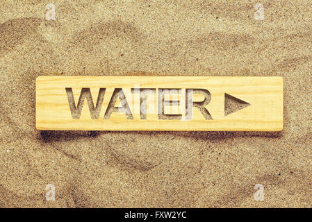 Water direction sign in dry desert sand, guide signpost for thirsty man. - Stock Photo