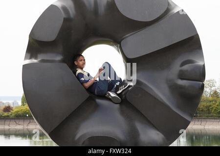 Seattle, Washington: Boy resting on Isamu Noguchi's 'Black Sun' in Volunteer Park. - Stock Photo