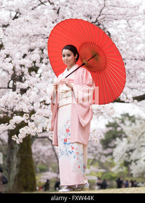 Portrait of young Japanese woman wearing kimono with cherry blossom in Shinjuku Gyoen Park, Tokyo, Japan, - Stock Photo